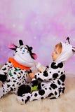 Μωρό στο κοστούμι αγελάδων που ταΐζει μια μασκότ αγελάδων Στοκ φωτογραφία με δικαίωμα ελεύθερης χρήσης