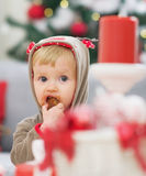 Μωρό στο κοστούμι Χριστουγέννων που τρώει το μπισκότο Στοκ Εικόνες