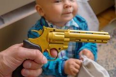 Μωρό ύπνου με ένα πυροβόλο όπλο στα χέρια του Στοκ Εικόνες