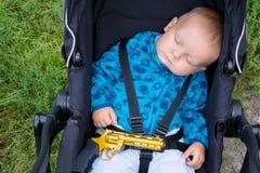 Μωρό ύπνου με ένα πυροβόλο όπλο στα χέρια του Στοκ φωτογραφίες με δικαίωμα ελεύθερης χρήσης