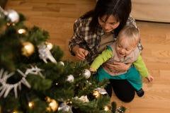 Μωρό moy στην περιτύλιξη μητέρων ` s τα Χριστούγεννα διακοσμούν τις φρέσκες βασικές ιδέες διακοσμήσεων Στοκ Εικόνες