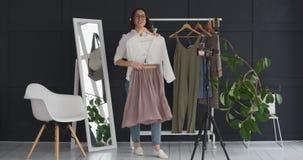 Μόδα vlogger που παρουσιάζει νέο φόρεμα μπροστά από τα κινητά βιντεοκάμερα φιλμ μικρού μήκους