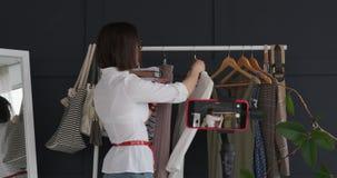 Μόδα vlogger που παρουσιάζει το νέο φόρεμα μπροστά από τα κινητά βιντεοκάμερα απόθεμα βίντεο