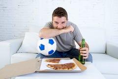 Μόνα σφαίρα εκμετάλλευσης νεαρών άνδρων και ποδοσφαιρικό παιχνίδι προσοχής μπουκαλιών μπύρας στον καναπέ τηλεοπτικών στο σπίτι κα Στοκ Εικόνες
