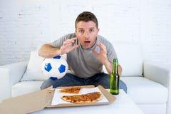 Μόνα σφαίρα εκμετάλλευσης νεαρών άνδρων και ποδοσφαιρικό παιχνίδι προσοχής μπουκαλιών μπύρας στον καναπέ τηλεοπτικών στο σπίτι κα Στοκ Φωτογραφία