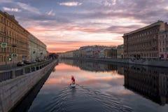 Μόνες κινήσεις γουλιάς surfer κατά μήκος του ποταμού Fontanka στην αυγή στοκ φωτογραφίες