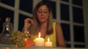 Μόνη γυναίκα που έχει το γεύμα σε ένα φωτισμένο με κεριά εστιατόριο, πίνοντας το κρασί που τρώει τα φρούτα απόθεμα βίντεο