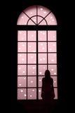 Μόνη γυναίκα που κοιτάζει μέσω του μεγάλου παραθύρου Στοκ Εικόνα
