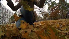Μόνη γυναίκα που περπατά μέσω του πάρκου φθινοπώρου, που ρίχνει επάνω στα πεσμένα χρυσά φύλλα απόθεμα βίντεο