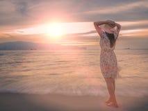 Μόνη και καταθλιπτική γυναίκα που κρατά ένα καπέλο και που στέκεται μπροστά από τη θάλασσα Στοκ εικόνα με δικαίωμα ελεύθερης χρήσης
