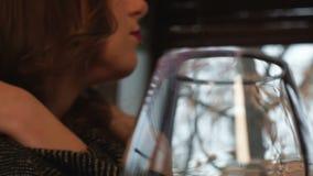Μόνη καταθλιπτική γυναίκα με το ποτήρι του κονιάκ που εξετάζει το παράθυρο, χειμερινή διάθεση απόθεμα βίντεο