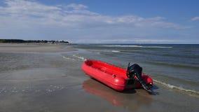 Μόνη κόκκινη λαστιχένια λέμβος με την εξωτερική μηχανή at low tide στη θάλασσα της Βαλτικής στοκ εικόνες