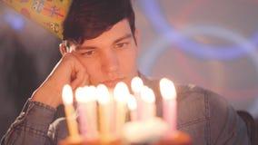 Μόνη λυπημένη συνεδρίαση αγοριών μπροστά από λίγο κέικ με τα αναμμένα κεριά που κοιτάζουν σε το Το δυστυχισμένο άτομο έχει τη γιο απόθεμα βίντεο