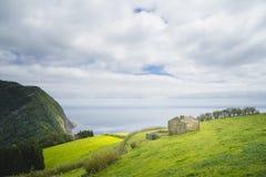 Μόνη μικρή καμπίνα στην άκρη του νησιού των Αζορών στην Πορτογαλία με μια μεγάλη άποψη στον Ατλαντικό Ωκεανό και το νεφελώδη ουρα Στοκ Φωτογραφία