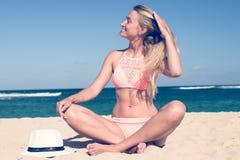 Μόνη νέα προκλητική συνεδρίαση γυναικών στην τροπική παραλία θαλασσίως με το καπέλο και στο μαγιό Διακοπές νησιών του Μπαλί Στοκ Εικόνες