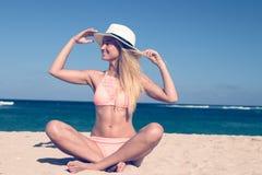 Μόνη νέα προκλητική συνεδρίαση γυναικών στην τροπική παραλία θαλασσίως με το καπέλο και στο μαγιό Διακοπές νησιών του Μπαλί Στοκ φωτογραφία με δικαίωμα ελεύθερης χρήσης