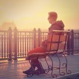 Μόνη συνεδρίαση ατόμων σε έναν πάγκο κατά τη διάρκεια του ηλιοβασιλέματος Συνεδρίαση ο νεαρών άνδρων Στοκ εικόνες με δικαίωμα ελεύθερης χρήσης