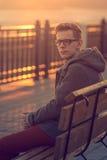 Μόνη συνεδρίαση ατόμων σε έναν πάγκο κατά τη διάρκεια του ηλιοβασιλέματος Πορτρέτο του νέου Μ Στοκ εικόνες με δικαίωμα ελεύθερης χρήσης