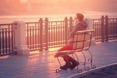Μόνη συνεδρίαση ατόμων σε έναν πάγκο κατά τη διάρκεια του ηλιοβασιλέματος Συνεδρίαση ο νεαρών άνδρων Στοκ Εικόνες
