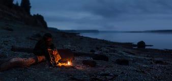 Μόνη ady συνεδρίαση οδοιπόρων από τη φωτιά στην ακτή ποταμών Εστίαση στην πυρκαγιά και τα πόδια Στοκ φωτογραφία με δικαίωμα ελεύθερης χρήσης