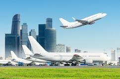 Μόνιμα αεροπλάνα ποδιών αερολιμένων και απογείωση επάνω από τους ουρανοξύστες στη μητρόπολη απόστασης στοκ εικόνες