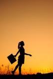 μόνιμη γυναίκα ηλιοβασιλέματος επιχειρησιακών σκιαγραφιών Στοκ Φωτογραφία