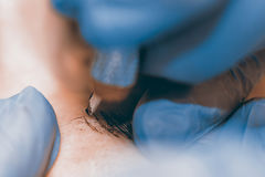 Μόνιμος αποτελέστε Cosmetologist που εφαρμόζει το μόνιμο makeup στο ey στοκ φωτογραφίες