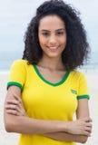 Μόνιμος βραζιλιάνος αθλητικός ανεμιστήρας με τη σγουρή τρίχα και τα διασχισμένα όπλα Στοκ Φωτογραφία