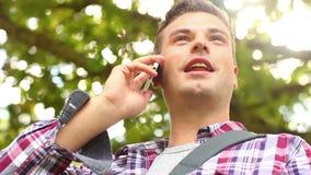 Μόνιμο εξωτερικό σπουδαστών χαμόγελου που μιλά στο τηλέφωνο απόθεμα βίντεο