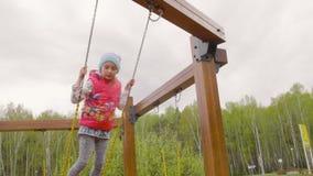 Μόνιμο κορίτσι εφήβων που ταλαντεύεται στην ημέρα άνοιξη στο πάρκο πόλεων σε αργή κίνηση φιλμ μικρού μήκους