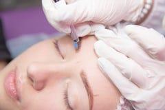 Μόνιμο Makeup για τα φρύδια Microblading brow Beautician που κάνει το φρύδι που διαστίζει για το θηλυκό πρόσωπο όμορφες νεολαίες στοκ φωτογραφία