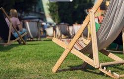 Μόνιππο -μόνιππο-longue κάτω από τον ήλιο στο πράσινο πάρκο με τους χαλαρώνοντας ανθρώπους Σαλόνι κήπων για την ηλιοθεραπεία και  Στοκ φωτογραφία με δικαίωμα ελεύθερης χρήσης