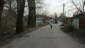 Μόνοι περίπατοι γυναικών κατά μήκος του δρόμου μεταξύ των σπιτιών και των δέντρων απόθεμα βίντεο