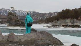 Μόνος θηλυκός τουρίστας που αναρριχείται στο βράχο στην όχθη ποταμού και που κοιτάζει γύρω Χειμώνας, καλυμμένο βουνά χιόνι φιλμ μικρού μήκους