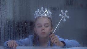 Μόνος λίγη πριγκήπισσα στην κορώνα με τη μαγική συνεδρίαση ραβδιών πίσω από το βροχερό παράθυρο απόθεμα βίντεο