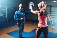 Μόνος-υπεράσπιση γυναικών workout με τον προσωπικό εκπαιδευτή στοκ εικόνες