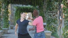 Μόνος-υπεράσπιση workout με τον εκπαιδευτή υπαίθρια Νέος μαύρος πλεκτό punching άσκησης καπέλων με τον προσωπικό εκπαιδευτή μέσα απόθεμα βίντεο