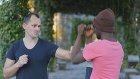 Μόνος-υπεράσπιση workout με τον εκπαιδευτή υπαίθρια Νέος μαύρος στις πλεκτές μόνος-αμυντικές τεχνικές άσκησης καπέλων με φιλμ μικρού μήκους