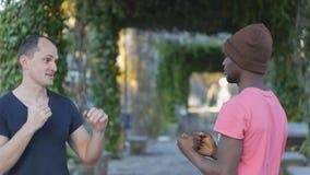 Μόνος-υπεράσπιση workout με τον εκπαιδευτή υπαίθρια Νέος μαύρος στις πλεκτές μόνος-αμυντικές τεχνικές άσκησης καπέλων με απόθεμα βίντεο