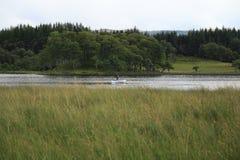 Μόνος ψαράς με το κάστρο Kilchurn, στο lochAwe σε Higlands της Σκωτίας στοκ φωτογραφίες