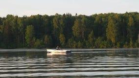 Μόνο άτομο που οδηγά σε μια βάρκα κωπηλασίας στο χρόνο σούρουπου λιμνών Ανατολή ηλιοβασιλέματος στη λίμνη Έννοια φύσης ελεύθερου  φιλμ μικρού μήκους