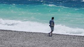 Μόνο άτομο που περπατά κατά μήκος της ακτής, απολαμβάνοντας τον ήχο των κυμάτων και του ευχάριστου αερακιού απόθεμα βίντεο