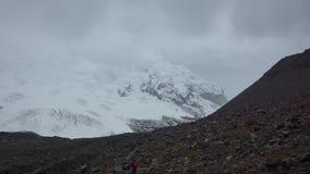 Μόνο άτομο που πλησιάζει τον παγετώνα του ηφαιστείου Antisana μια νεφελώδη ημέρα στην οικολογική επιφύλαξη Antisana Στοκ Εικόνα