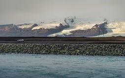 Μόνο αυτοκίνητο με το πρώτο πλάνο θάλασσας και τη σειρά βουνών χιονιού Στοκ Φωτογραφίες