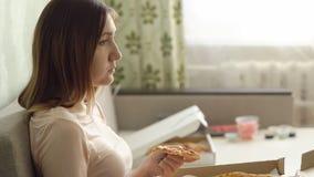 Μόνο λυπημένο κορίτσι με τη συνεδρίαση πιτσών στον καναπέ στο σπίτι και τα ρολόγια ένας κινηματογράφος Στοκ φωτογραφία με δικαίωμα ελεύθερης χρήσης