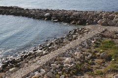 Μόνο μαύρο περιστέρι στο γείσο ενός τοίχου πετρών Στοκ Φωτογραφία