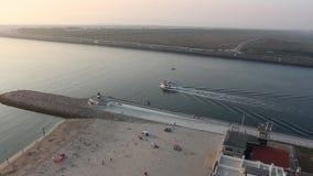 Μόνο σκάφος που ταξιδεύει ήπια μια λιμνοθάλασσα δίπλα σε μια παραλία Παραλία Barra από το Αβέιρο, Πορτογαλία φιλμ μικρού μήκους