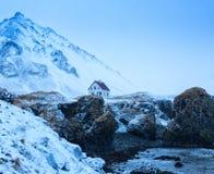 Μόνο σπίτι πίσω από τους απότομους βράχους κοντά στο χωριό Arnarstapi στο σούρουπο το χειμώνα, Snaefellsnes, Ισλανδία Στοκ εικόνα με δικαίωμα ελεύθερης χρήσης