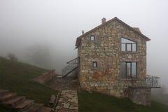 Μόνο σπίτι πετρών στο λόφο στην ομίχλη, πλάγια όψη στοκ φωτογραφίες με δικαίωμα ελεύθερης χρήσης
