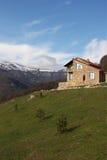 Μόνο σπίτι πετρών στο λόφο στο υπόβαθρο των χιονωδών βουνών, κάθετο στοκ εικόνα με δικαίωμα ελεύθερης χρήσης